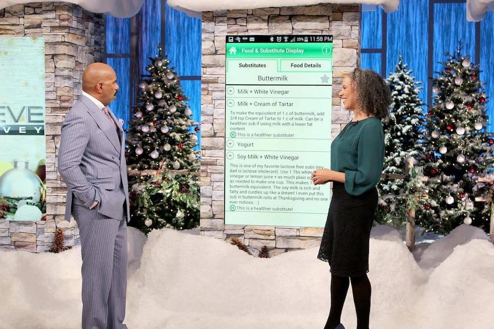A man and woman standing in front of a fake snow scene on a tv studio stage with recipe ingredients on a greenscreen behind them.
