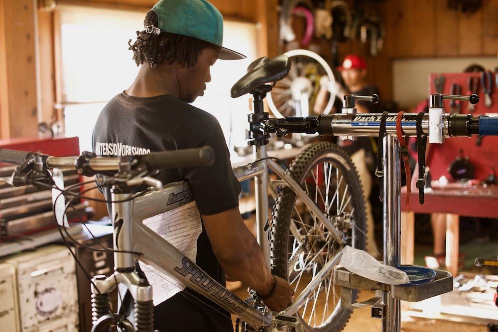 Youth working on a bike in the bike shop.