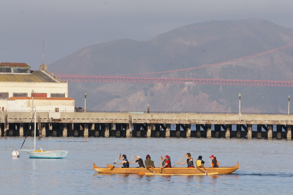 Youth paddling a boat in the San Francisco Bay with Golden Gate Bridge in the background.