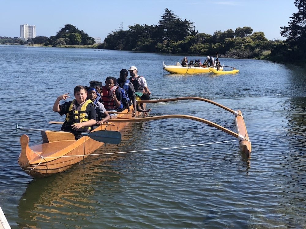 Kids paddling an outrigger boat