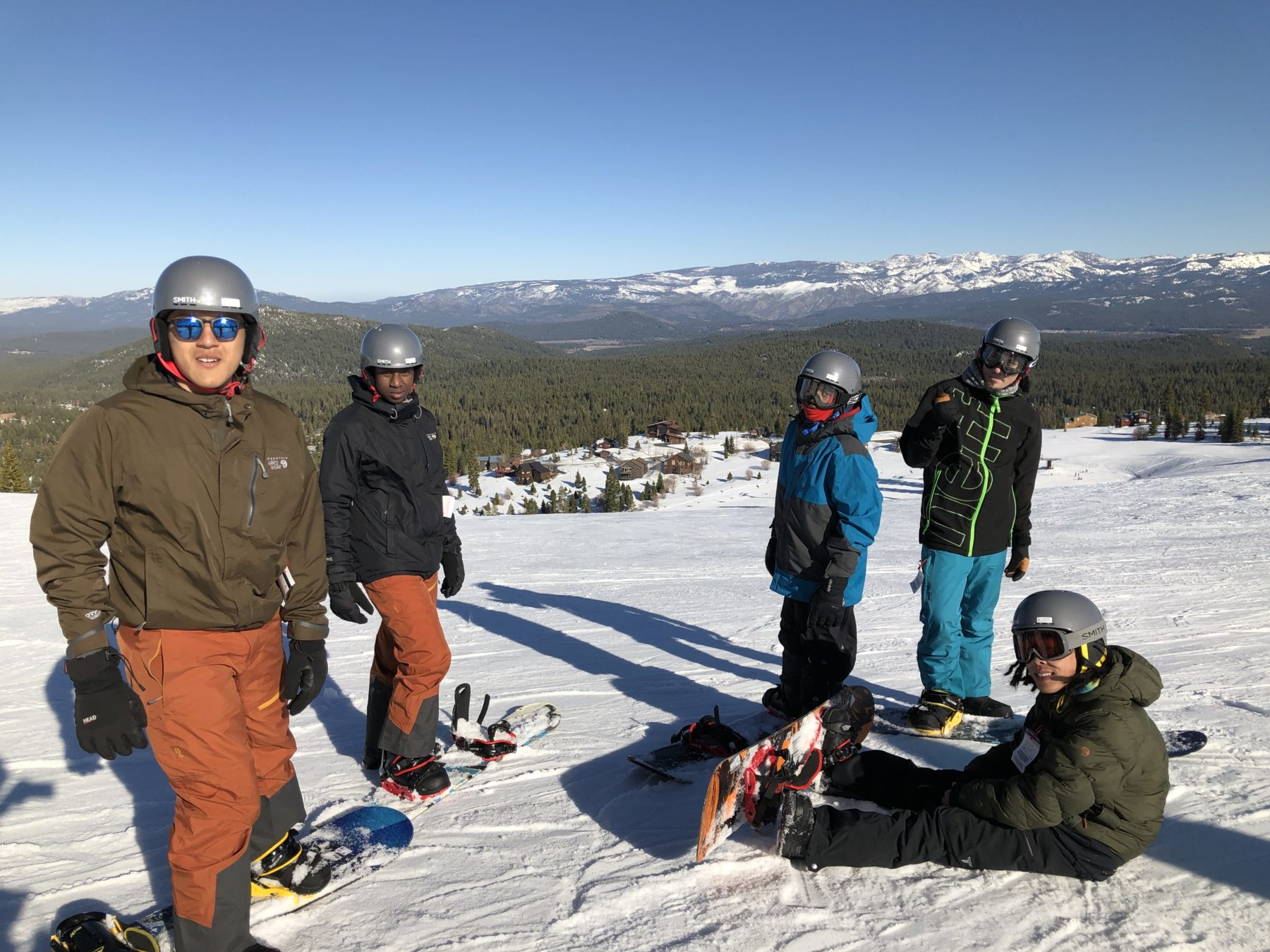 Youth on snowboards at top of mountain with snowcapped mountains in the background.
