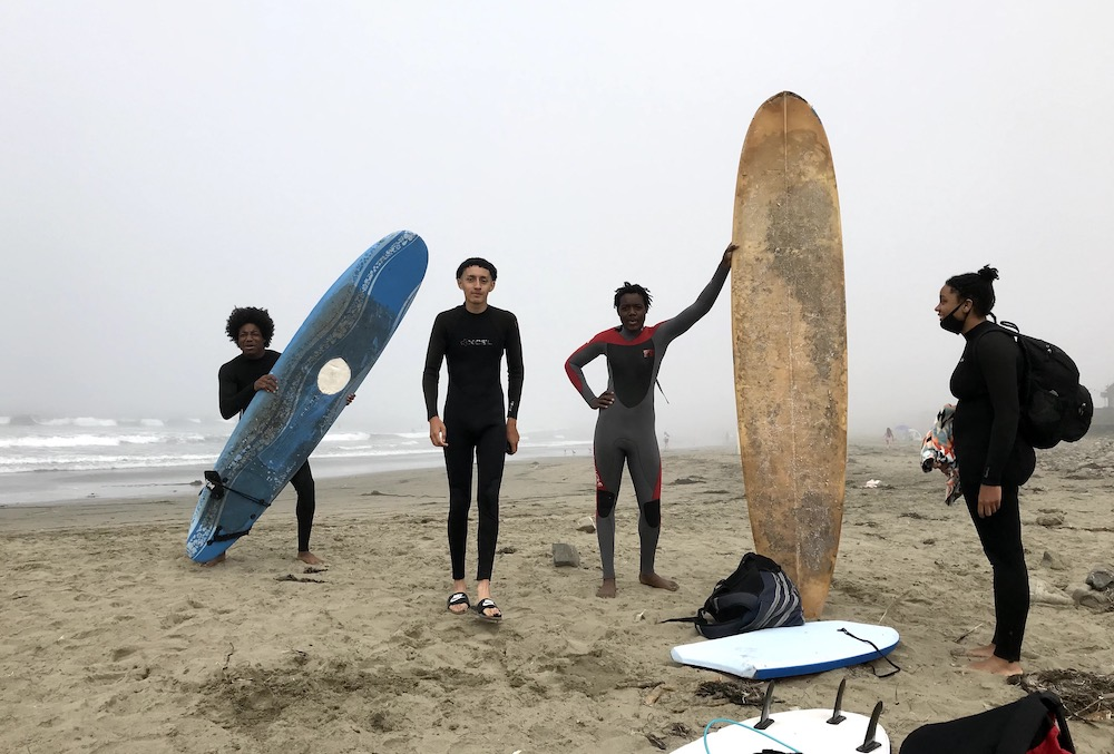 Youth on a foggy beach with surfboards.