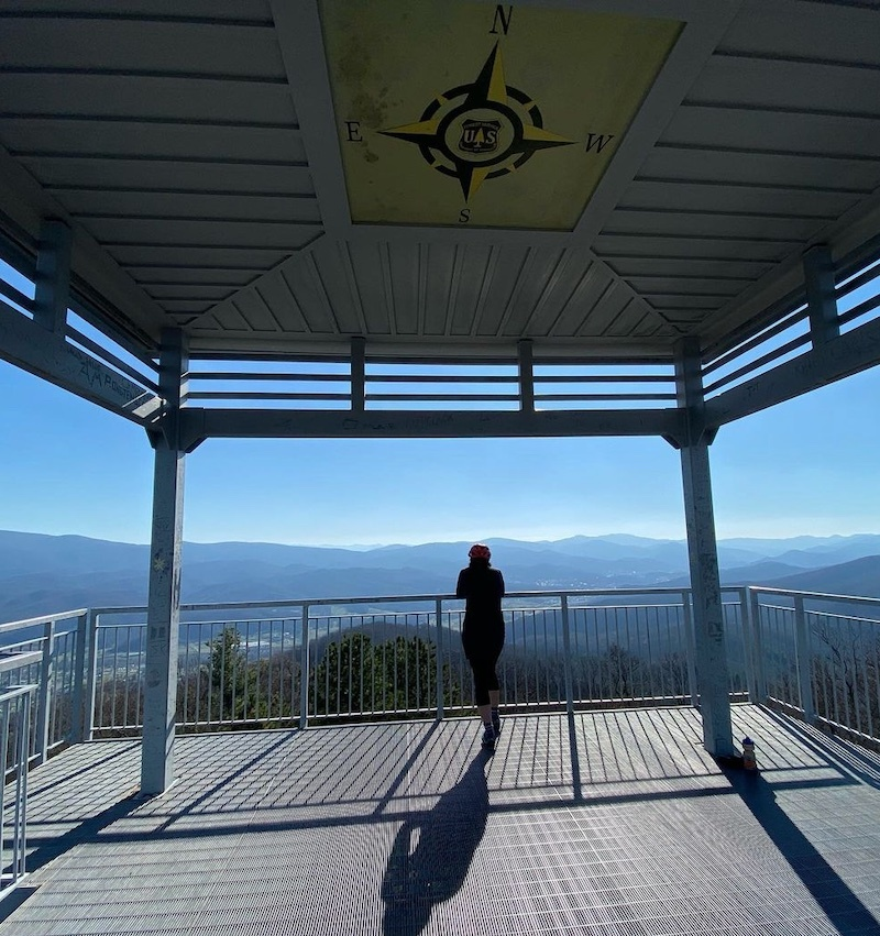 A woman who works at a digital marketing agency in Asheville standing on top of a fire tower with a compass painted on the ceiling above her. She's looking out at blue ridge mountains.