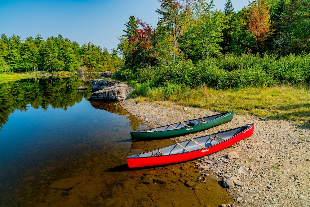 A red and green canoe sitting on the banks of a lake